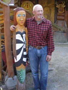 "Wood carver Russ Zeitz with his ""Birdfishwoman"" sculpture"